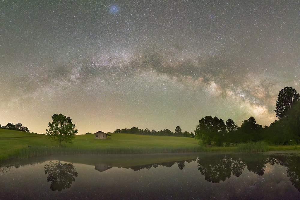 The full length of the Milky Way is spread across the countryside hills and an old shed, reflected in a small pond below at the dark sky reserve of Calhoun County Park in West Virginia.