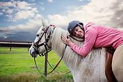 Mature women riding a horse looking at camera.