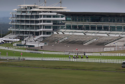 © Licensed to London News Pictures. 04/07/2020. Epsom, UK. Riders in The Investec Surrey Stakes Derby Day race pass an empty grandstand as they near the finish. Today's race meeting is being held behind closed doors due to the coronavirus lockdown rules. Seven races are being held in one day including The Oaks, with The Derby being run at 4:55pm. Photo credit: Peter Macdiarmid/LNP