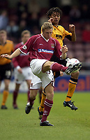 Photo: Richard Lane.<br />Northampton Town v Hull City. Nationwide Division Three. 04/10/2003.<br />Chris Carruthers gets the ball away as Jason Price puts on the pressure.