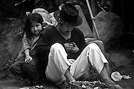 A young girl is watching her father crafting souveniers in Otavalo.