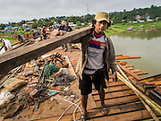 16 SEPTEMBER 2014 - SANGKHLA BURI, KANCHANABURI, THAILAND: Members of the Mon community carry wood to be used on the deck of the Mon Bridge to the construction area on the bridge. The 2800 foot long (850 meters) Saphan Mon (Mon Bridge) spans the Song Kalia River. It is reportedly second longest wooden bridge in the world. The bridge was severely damaged during heavy rainfall in July 2013 when its 230 foot middle section  (70 meters) collapsed during flooding. Officially known as Uttamanusorn Bridge, the bridge has been used by people in Sangkhla Buri (also known as Sangkhlaburi) for 20 years. The bridge was was conceived by Luang Pho Uttama, the late abbot of of Wat Wang Wiwekaram, and was built by hand by Mon refugees from Myanmar (then Burma). The wooden bridge is one of the leading tourist attractions in Kanchanaburi province. The loss of the bridge has hurt the economy of the Mon community opposite Sangkhla Buri. The repair has taken far longer than expected. Thai Prime Minister General Prayuth Chan-ocha ordered an engineer unit of the Royal Thai Army to help the local Mon population repair the bridge. Local people said they hope the bridge is repaired by the end November, which is when the tourist season starts.    PHOTO BY JACK KURTZ