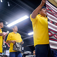 Larry Holona displays a rug for the crowd during the monthly Crownpoint Rug Auction at Crownpoint Elementary School April 8.