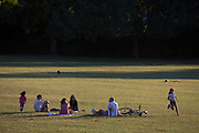 With the UK death toll reaching 38,489, a further 113 victims in the last 24hrs, and the government's pandemic lockdown still in effect, children race around other south Londoners practicing social distances in Ruskin Park, a public green space in the borough of Lambeth, on 31st May 2020, in London, England.