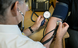 EMBARGOED TO 0001 FRIDAY MAY 03 File photo dated 10/09/14 of a GP checking a patient's blood pressure. At least six UK regions running out-of-hours services had no GP on shift at least once last year, data suggests.