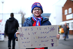 A young Crystal Palace fan holds up a sign reading 'This is my 1st game can I please, please have a shirt' during the Premier League match at Selhurst Park, London.