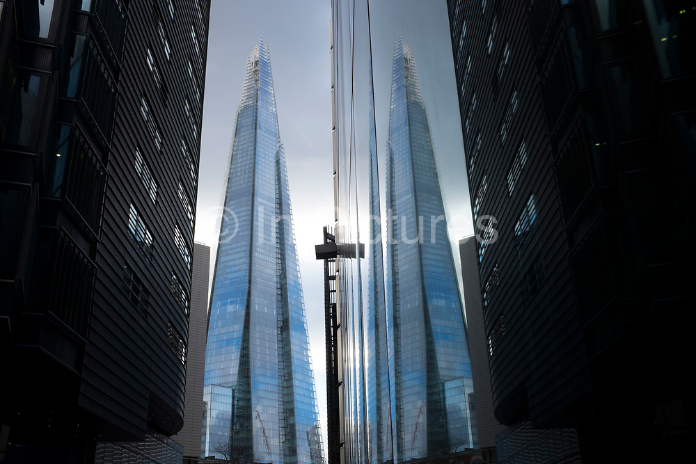 The Shard reflected in double against tall buildings at More London, UK. The Shard, also referred to as the Shard of Glass, Shard London Bridge and formerly London Bridge Tower, is an 87-storey skyscraper in London that forms part of the London Bridge Quarter development.