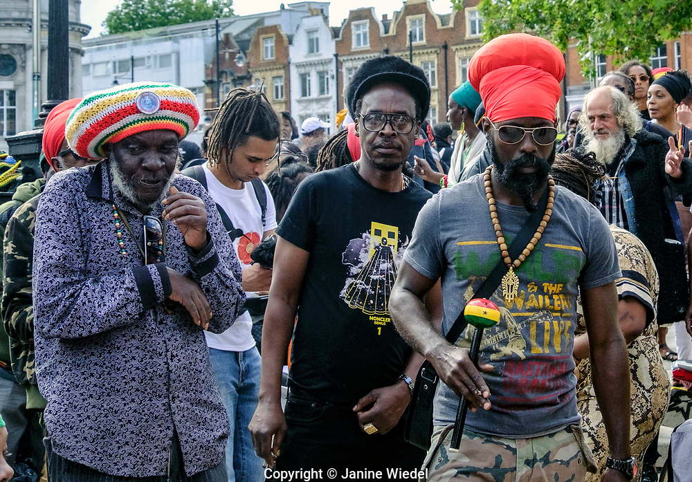Rastafarian men dancing to and enjoying Groundation music at annual Reparations Rebellion event on Afrikan Emancipation Day in Windrush Square Brixton 2021.