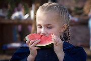 "Aug 9, 2008 -- COLORADO CITY, AZ:  A girl eats a slice of watermelon during a picnic at the family home in Colorado City, AZ. Colorado City and neighboring town of Hildale, UT, are home to the Fundamentalist Church of Jesus Christ of Latter Day Saints (FLDS) which split from the mainstream Church of Jesus Christ of Latter Day Saints (Mormons) after the Mormons banned plural marriage (polygamy) in 1890 so that Utah could gain statehood into the United States. The FLDS Prophet (leader), Warren Jeffs, has been convicted in Utah of ""rape as an accomplice"" for arranging the marriage of teenage girl to her cousin and is currently on trial for similar, those less serious, charges in Arizona. After Texas child protection authorities raided the Yearning for Zion Ranch, (the FLDS compound in Eldorado, TX) many members of the FLDS community in Colorado City/Hildale fear either Arizona or Utah authorities could raid their homes in the same way. Older members of the community still remember the Short Creek Raid of 1953 when Arizona authorities using National Guard troops, raided the community, arresting the men and placing women and children in ""protective"" custody. After two years in foster care, the women and children returned to their homes. After the raid, the FLDS Church eliminated any connection to the ""Short Creek raid"" by renaming their town Colorado City in Arizona and Hildale in Utah. A member of the Jessop family weeds the community corn plot in Colorado City, AZ. The Jessops are a polygamous family and members of the FLDS.  Photo by Jack Kurtz / ZUMA Press"