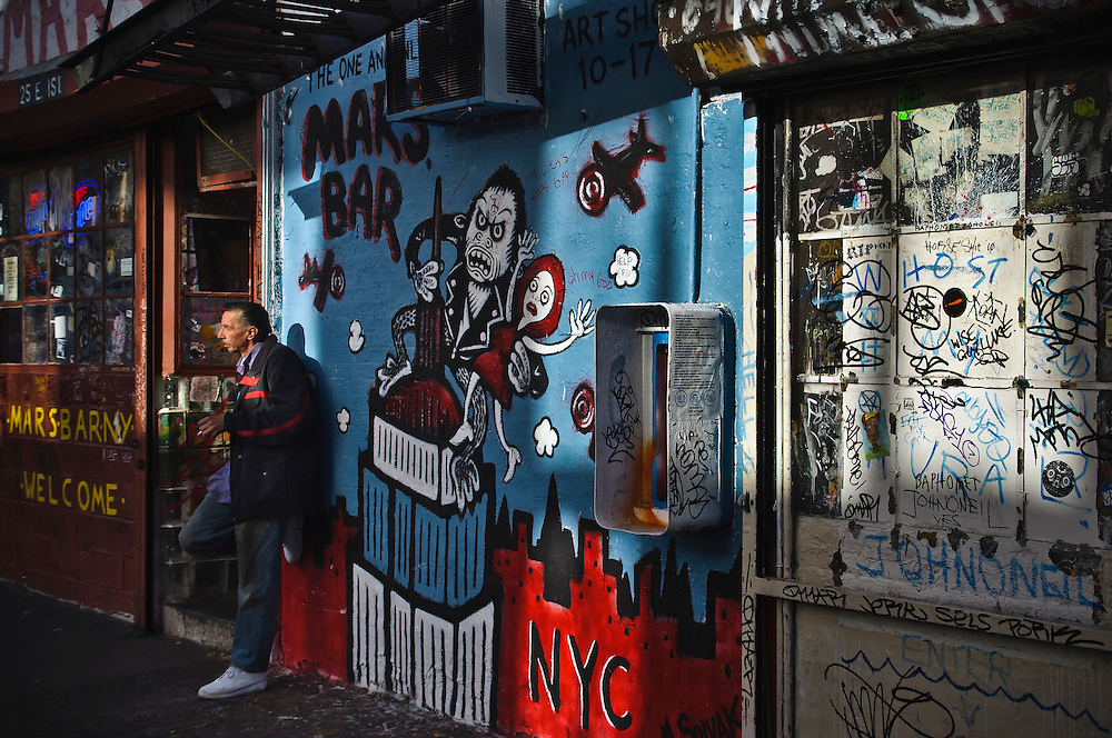 A man smokes a cigarette outside the Mars Bar in the Lower East side, Manhattan, New York, 2010.