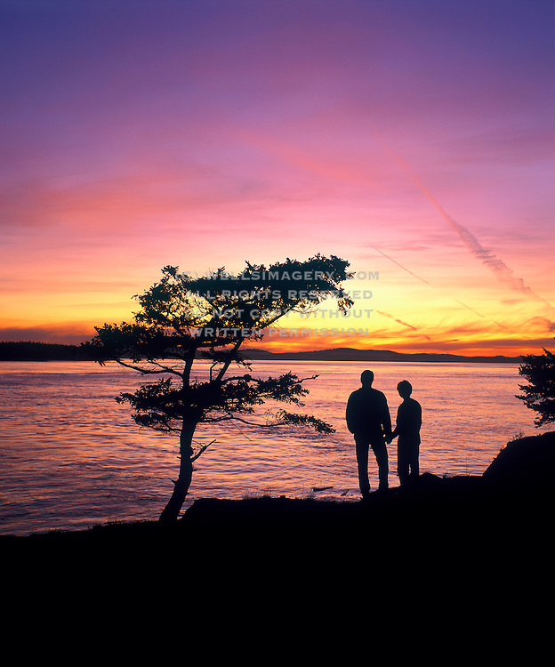 Image of a couple at Shark Reef Park at sunset, Lopez Island, San Juans, Washington, Pacific Northwest, model released by Randy Wells