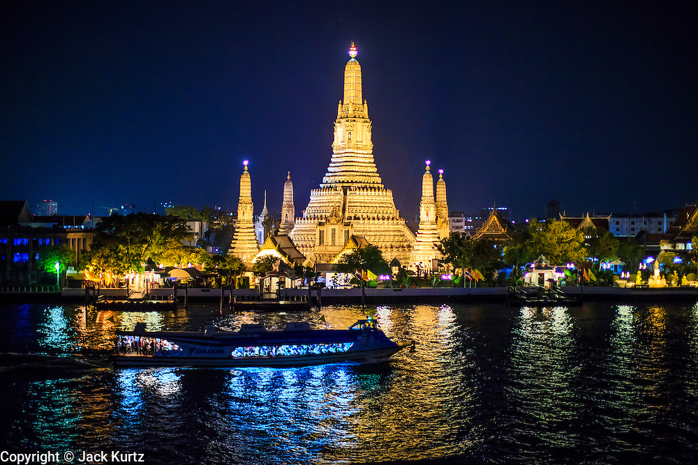 "23 SEPTEMBER 2013 - BANGKOK, THAILAND:  Wat Arun, on the west bank of the Chao Phraya River, in Bangkok. The full name of the temple is Wat Arunratchawararam Ratchaworamahavihara. The outstanding feature of Wat Arun is its central prang (Khmer-style tower). The world-famous stupa, known locally as Phra Prang Wat Arun, will be closed for three years to undergo repairs and renovation along with other structures in the temple compound. This will be the biggest repair and renovation work on the stupa in the last 14 years. In the past, even while large-scale work was being done, the stupa used to remain open to tourists. It may be named ""Temple of the Dawn"" because the first light of morning reflects off the surface of the temple with a pearly iridescence. The height is reported by different sources as between 66,80 meters and 86 meters. The corners are marked by 4 smaller satellite prangs. The temple was built in the days of Thailand's ancient capital of Ayutthaya and originally known as Wat Makok (The Olive Temple). King Rama IV gave the temple the present name Wat Arunratchawararam. Wat Arun officially ordained its first westerner, an American, in 2005. The central prang symbolizes Mount Meru of the Indian cosmology. The temple's distinctive silhouette is the logo of the Tourism Authority of Thailand.          PHOTO BY JACK KURTZ"