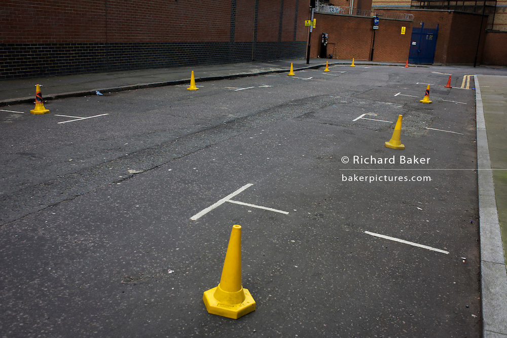 Yellow cones prevent parking in a London side-street.