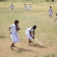 Girl students play cricket in the grounds of the Vadamunai Government Tamil Mixed School in Batticaloa District. <br /> <br /> When fighting between the LTTE and Colombo Government forced the displacement of the local Tamil community in 2007, the Vadamunai Government Tamil Mixed School in Batticaloa District was closed. Since reopening in January 2009, the school has six teaching staff for 88 pupils from Grades 1-9. Before closure,136 pupils studied at the school. Poor road-infrastructure and the remote location of the school means that many staff have to commute for more than three hours. Five classes are held in a UNICEF-supplied Temporary Learning Space. Four other classes are conducted outside, beneath treesa. Many of the students suffer with the trauma and stress associated with those living in conflict situations. The staff must deal with these issues as well as the personal difficulties that they themselves suffer living in a conflict environment. To further antagonise an already difficult situation, the school suffers the very real danger of wild-elephant encroachment on their grounds. The school encourages gender-equality and has a meals program, providing some students their only square meal in the day. <br /> <br /> Photo: Tom Pietrasik<br /> Batticaloa District, Sri Lanka<br /> September 30th 2009