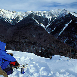A hiker looks out at Franconia Ridge from the Old Bridal Path. Snow.  Old Bridle Path, Mt. Lafayette, NH