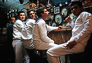 Sailors sitting on stools at a bar in Italy 1966
