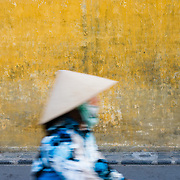 Woman in traditional clothing passing yellow wall of Hoi An Ancient Town
