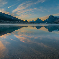 Mist rises over Bow Lake as dawn breaks on (L to R) Cirque Peak, Mount Andromache, Mount Hector, Bow Peak, Bow Crow Peak and Crowfoot Mountain in Banff National Park, Alberta, Canada.