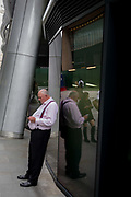 A businessman wearing braces over a large tummy checks his mobile phone messages, on 11th August, 2017, in the City of London, England.