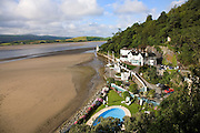 """Portmeirion, in North Wales, is a resort, where no one has ever lived. A self-taught Welsh architect named Sir Clough Williams-Ellis built it out of architectural salvage between the 1920s and 1970s, loosely based on his memories of trips to Portofino. Including a pagoda-shaped Chinoiserie gazebo, some Gothic obelisks, eucalyptus groves, a crenellated castle, a Mediterranean bell tower, a Jacobean town hall, and an Art Deco cylindrical watchtower. He kept improving Portmeirion until his death in 1978, age 94. It faces an estuary where at low tide one can walk across the sands and look out to sea. At high tide, the sea is lapping onto the shores. Every building in the village is either a shop, restaurant, hotel or self-catering accomodation. The village is booked out at high season, with numerous wedding receptions at the weekends. Very popular amongst the English and Welsh holidaymakers. Many who return to the same abode season after season. Hundreds of tourists visit every day, walking around the ornamental gardens, cobblestone paths, and shopping, eating ice-creams, or walking along the woodland and coastal paths, amongst a colourful assortment of hydrangea, rhododendrons, tree ferns and redwoods. The resort boasts two high class hotels, a la carte menus, a swimming pool, a lifesize concrete boat, topiary, pools and wishing wells. The creator describes the resort as """"a home for fallen buildings,"""" and its ragged skyline and playful narrow passageways which were meant to provide """"more fun for more people."""" It does just that.///Portmeirion Hotel overlooking the estuary Afon Dwyryd towards Porthmadog and Tremadog."""