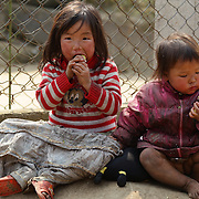 Young Black Hmong children eat food in a local villiage near Sapa, Northern Vietnam.  Sapa and the surrounding highlands are close to the Chinese border in Northern Vietnam and is inhabited by highland minorities including Hmong and Dzao groups. Sapa is now a thriving tourist destination for travelers taking the night train from Hanoi. Sapa, Vietnam. 16th March 2012. Photo Tim Clayton