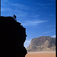 A climber ascends a boulder in Jordan's Wadi Rum, near the edge of the Arabian Desert.