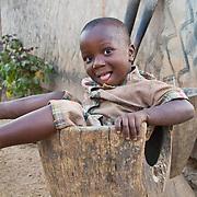 Little Djibi finds out how it feels to enter the millet pounder. Koumbadiouma, Kolda, Senegal.