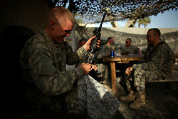 A paratrooper with Alpha Battery 2-319 2BCT 82nd Airborne Division cleans his weapon during down time at the Sleikh Joint Security Station in Baghdad's Adhamiya District on Thursday April 26, 2007.