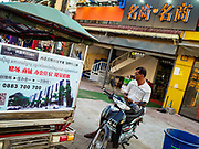 """14 FEBRUARY 2019 - SIHANOUKVILLE, CAMBODIA:  A Cambodian man sits on his motorcycle sandwhiched between a tuk-tuk with a Chinese real estate project and a Chinese shop in Sihanoukville. There are about 80 Chinese casinos and resort hotels open in Sihanoukville and dozens more under construction. The casinos are changing the city, once a sleepy port on Southeast Asia's """"backpacker trail"""" into a booming city. The change is coming with a cost though. Many Cambodian residents of Sihanoukville  have lost their homes to make way for the casinos and the jobs are going to Chinese workers, brought in to build casinos and work in the casinos.      PHOTO BY JACK KURTZ"""