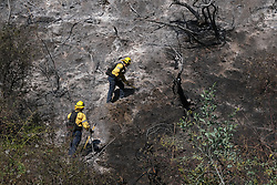 October 29, 2019, Los Angeles, California, USA: Firefighters work in extreme terrain along the 405 freeway near the Getty Center to put out hot spots Tuesday. An extreme red flag Santa Ana wind condition with 50-70 mph wind gusts is expected to begin late Tuesday into Wednesday. (Credit Image: © David Crane/Orange County Register via ZUMA Wire)