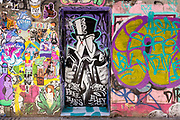Freeman Alley, the Bowery, New York City. A tuxedoed and top-hatted figure on a door, flanked by hundreds of tags on one side, and large spray painted graphic tags on the other.
