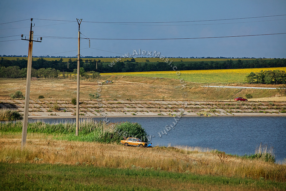 A Ukrainian man is fishing in a pond while crouching next to his Lada car, near Mariupol, southeast Ukraine.