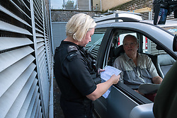 © Licensed to London News Pictures. 24/09/2019. Bristol, UK. Picture of the landlord owner in car (did not give name) with police reading the legal paperwork. Bailiffs from EAS Enforcement with the landlord and agents and police present, and being filmed by Channel 5 for television, attempt an eviction at 26 Picton Lane, Montpelier. A resident (in flat cap) can be seen on the roof of a van and building as bailiffs use a scissor lift to try and access the roof, after supporters of the resident try and block the lift from being brought to the site. Photo credit: Simon Chapman/LNP.