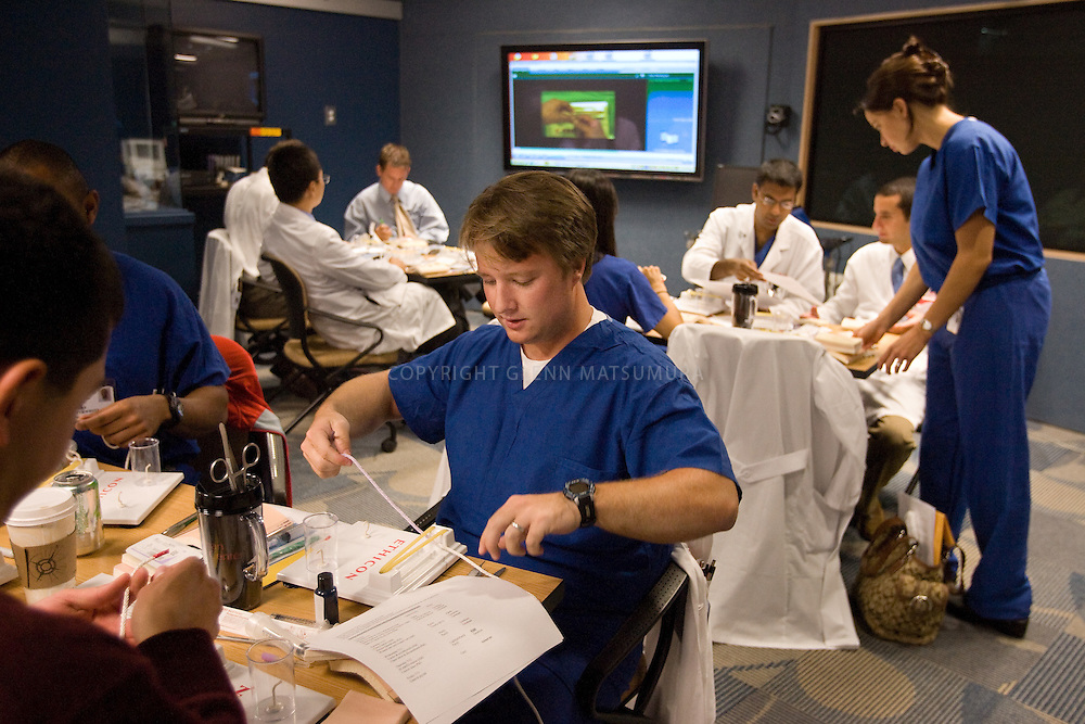 """Stanford Goodman Simulation lab """"boot camp"""" at Stanford Hospital. First year residents practice suturing on tissue pads. Owen Palmer practices tieing knots.  Mary-Anne Purtill, MD leads class. Other instructor: Catherine Mohr, MD (black top/slacks). Program director: Sandra Feaster, RN."""