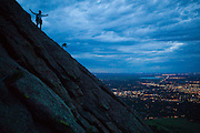 Obadiah Reid climbs the First Flatiron at night above Boulder, Colorado.