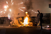 NOVEMBER 9, 2016 - OAKLAND, CA: A firework shot by Anti-Trump protesters explodes as protesters and Police confront each other on Telegraph Avenue in Uptown, after protesters dismantle construction barricades at the new Uber headquarters, to use as fodder for a fire, in Oakland, California on November 9, 2016. (Photo by Philip Pacheco)