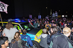 London, UK. 17th April 2019. A police vehicle is briefly trapped among drummers from climate change action movement Extinction Rebellion marching towards Westminster Bridge from Parliament Square during a police operation to clear protesters taking part in the International Rebellion in order to reopen the square to traffic.