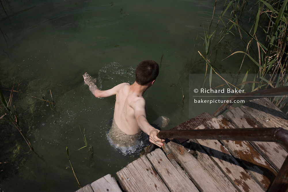 A 17 year-old boy enters a fresh water lake in Kaltern-Caldaro, south Tyrol, northern Italy.