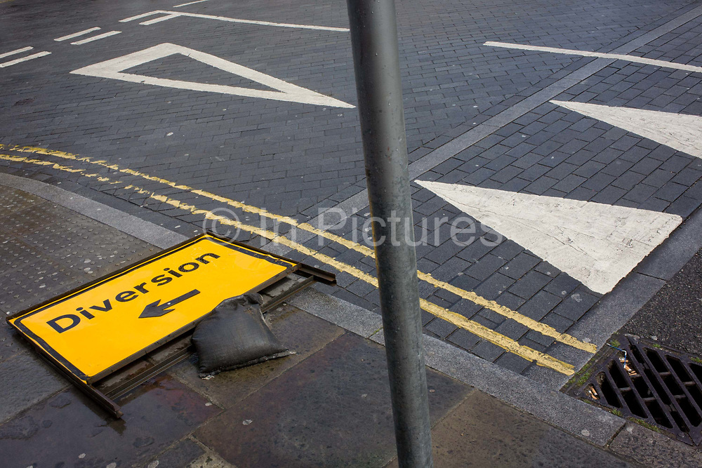 Aerial landscape of road diversion sign and road triangle markings. This is a detail of street and road markings, the geometry of shapes and linear design with the triangular points meeting at a diagonal post, the parallel lines in the road and the arrow of a diversion sign. The street is in Waterloo, called The Cut in the borough of Lambeth.