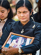 """19 DECEMBER 2016 - BANGKOK, THAILAND: A woman clutches her photo of Bhumibol Adulyadej, the Late King of Thailand, during a """"Spirit Appeasing"""" Ceremony held for the Royal Chariots at the Bangkok National Museum. The chariots will be used to take the body of Bhumibol Adulyadej, the Late King of Thailand, and members of the Royal funeral cortege to the cremation site on Sanam Luang for His Majesty's cremation. This will be the first cremation of a Thai King since 1950, when King Bumibol's brother, Rama VIII, Ananda Mahidol, was cremated. The design of the royal crematorium is based on Buddhist cosmology, with the main peak of Mount Sumeru (also known as Meru in Hindu cosmology) at center and eight other peaks signifying the levels of the universe. The crematorium will be decorated with mythical creatures such as garuda, angels, and Himmapan Forest creatures. The structure and funeral pyre will stand just over 50 meters tall. The exact date of the King's cremation has not been set yet but is expected to be late next year.     PHOTO BY JACK KURTZ"""