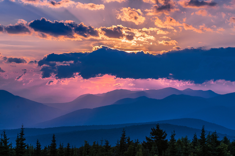 Sunrise behind thick clouds over mountains, pink, yellow and blue colors, Woodstock, NH