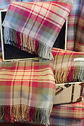 Traditional highland tartan called Auld Scotland as lambswool throws and scarves for sale at Lochcarron Weavers Shop in the Highlands of Scotland