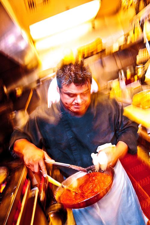 Geraldo Perez, cousin of executive Chef Martin Perez, prepares osso bucco with saffron risotto milanese, in the kitchen of Miami Beach's Osteria del Teatro.