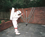 Space-suited frequent flyer astronaut Alan Watts plays moon-walker at his north London home, England. Alan, 51, runs an electrical company and qualified for a free space space flight after being contacted by Sir Richard Branson's Virgin Galactic space company, having accumulated 2 million air miles on the Virgin Atlantic flight network. Aboard the re-usable space vehicle will be 6 passengers, each of whom will have paid $200,000 for the 40 minute flight to 360,000 feet (109.73km, or 68.18 miles) and to experience just 6 minutes of weighlessness.   Flights start around 2009/10 from a Mojave desert test facility but therafter, at the new Philippe Starck-designed SpacePort America, New Mexico, USA. a 27 square mile, $225 million headquarters and mission control facility near Las Cruces.