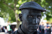 Portrait of Matt, from Mechanical Fracture (human statues) a living statue street performer painted a dark metallic greay colour and wearing a flat cap, like an old industrial worker character. The South Bank is a significant arts and entertainment district, and home to an endless list of activities for Londoners, visitors and tourists alike.