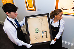 Sotheby's, Mayfair, London, November 7th 2014. Several outstanding examples of Czech avant-garde art from the Roy and Mary Cullen collection are to be auctioned by Sotheby's on November 12th. PICTURED: Sotheby's gallery workers prepare to hang Antonin Pelc's portrait of fellow avante garde artist Jindrich Styrsky.