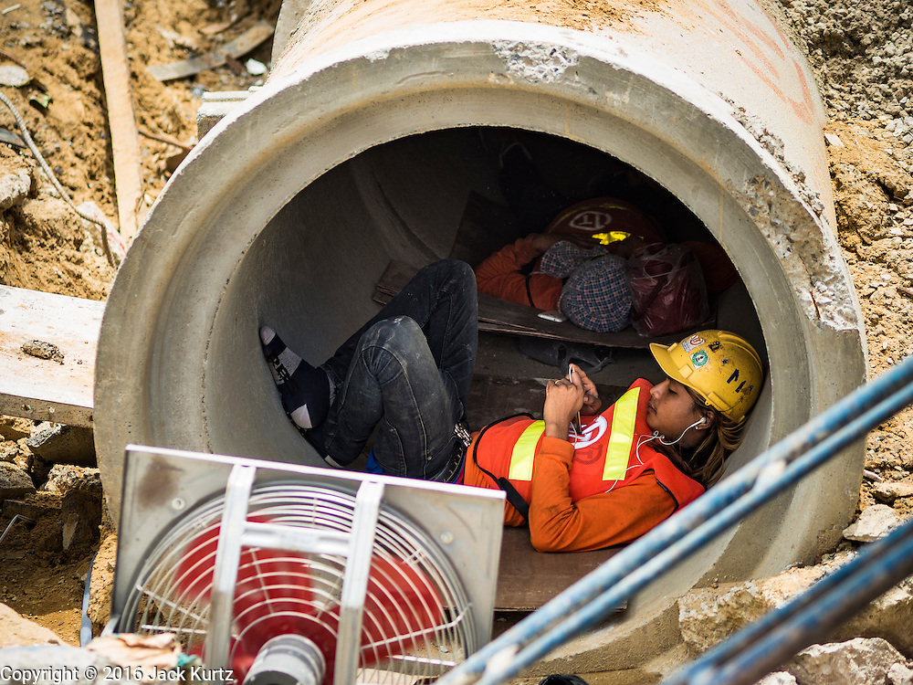 08 JUNE 2016 - BANGKOK, THAILAND:  Workers building the subway station at the intersection of Phlap Phla Chai and Chareon Krung Streets in Bangkok's Chinatown neighborhood escape the heat during a break in the construction day. The Bangkok Metropolitan Rapid Transit (MRT) system, Bangkok's subway, is being expanded through Chinatown and a station is under construction at the intersection. The small produce market at the intersection will have to move and several of the businesses near the intersection have been evicted to make way for the construction. Bangkok's Chinatown, considered by some to be one of the best preserved Chinatown districts in the world, is changing. Many of the old shophouses are being demolished and replaced by malls and condominium developments.     PHOTO BY JACK KURTZ
