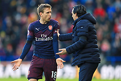 Arsenal's Nacho Monreal (left) and Arsenal manager Unai Emery speak during the Premier League match at the John Smith's Stadium, Huddersfield.