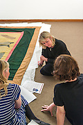 Artist Kate Scardifield during her research visit to the Scottish Borders,  as part of the 'Archival Enactments – New Constellations' project. This first part of her vsist took place between  27th June-  1st July and she visited various archives, artists, textile facilities, creatives and museums. <br /> At Hawick Musem she viewed parts of the Textile Collection with Shona Sinclair, the curator.  Items views included historic political and festival banners <br /> Kate Scardifield is an interdisciplinary artist living and working in Sydney. Her practice can be likened to a process of anatomical enquiry; mining history for intersecting systems and patterns that culminate in re-imaginings of the body, site and space. Scardifield's works traverse sculpture, installation, textiles, video and painting, often incorporating repetitious iconography and labour intensive techniques. Relationships between the spectacle, the macabre and the divine, in their broadest form, operate as cornerstones in her practice