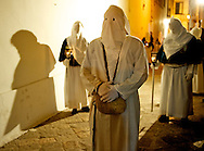 A hooded penitent bearing two heavy stones on his shoulders
